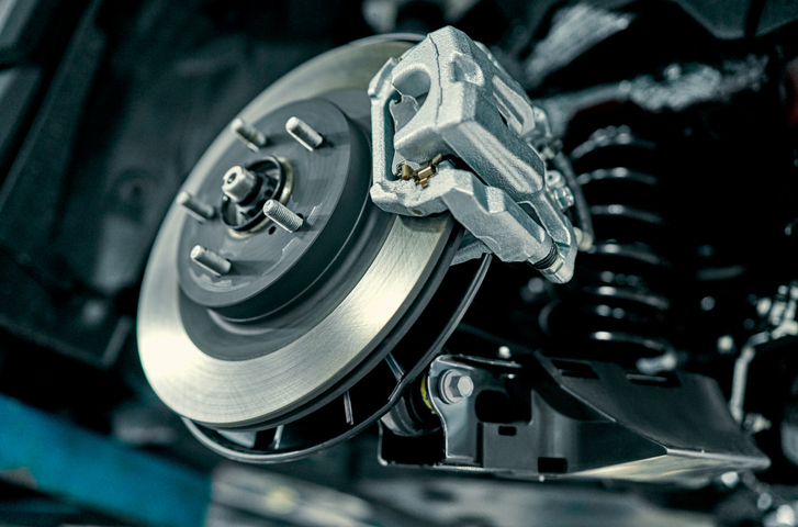 Disc brake of the vehicle for repair, in process of new tire replacement. Car brake repairing in garage.Suspension of car for maintenance brakes and shock absorber systems. Close up.